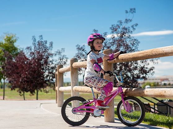 A girl on a pink bike with a pink helmet and arm pads