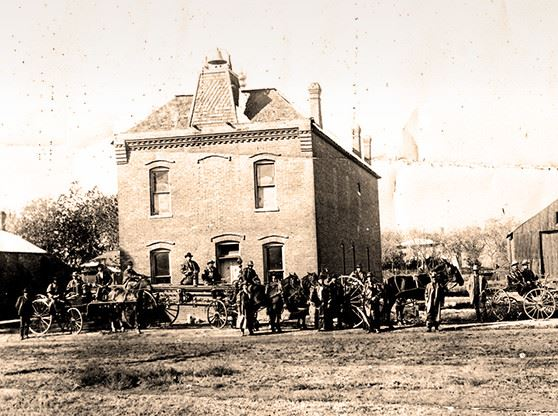 A black and white photo of a brick house with horses and carriages outside it