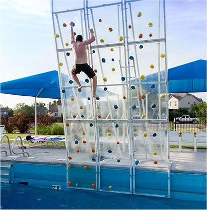 Man climbing rock wall at the edge of the pool