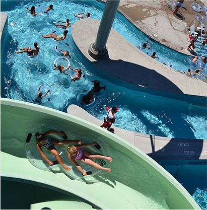 View from the top of a water slide looking down at two girls on water tube riding the slide and peop